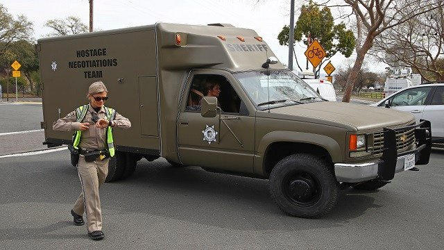 A sheriff's hostage negotiation team passes a California highway patrol checkpoint at the Veterans Home of California in Yountville, Calif., Friday, March 9, 2018.  (AP Photo/Ben Margot)