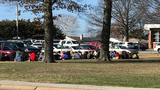 A group of high schoolers at Affton Schools is silently sitting in the front lawn as part of the Wednesday's national walk out. (Credit: KMOV)