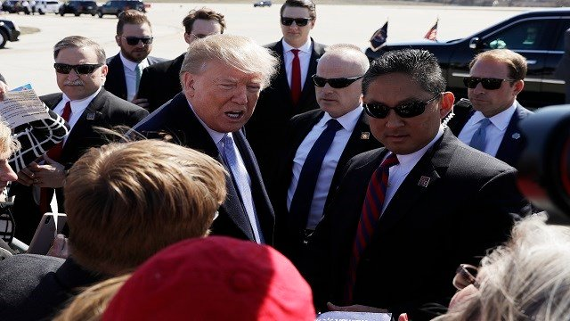 President Donald Trump greets supporters after arriving at St. Louis Lambert International Airport, Wednesday, March 14, 2018, in St. Louis. (AP Photo/Evan Vucci)