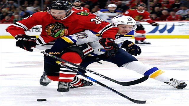 Chicago Blackhawks center Matthew Highmore, left, and St. Louis Blues center Brayden Schenn battle for the puck during the second period of an NHL hockey game Sunday, March 18, 2018, in Chicago. (AP Photo/Nam Y. Huh)