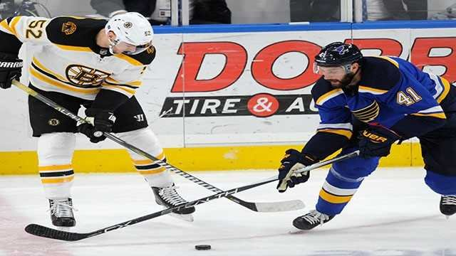 St. Louis Blues' Robert Bortuzzo (41) and Boston Bruins' Sean Kuraly (52) reach during the first period of an NHL hockey game Wednesday, March 21, 2018, in St. Louis. The Blues won in overtime, 2-1. (AP Photo/Bill Boyce)