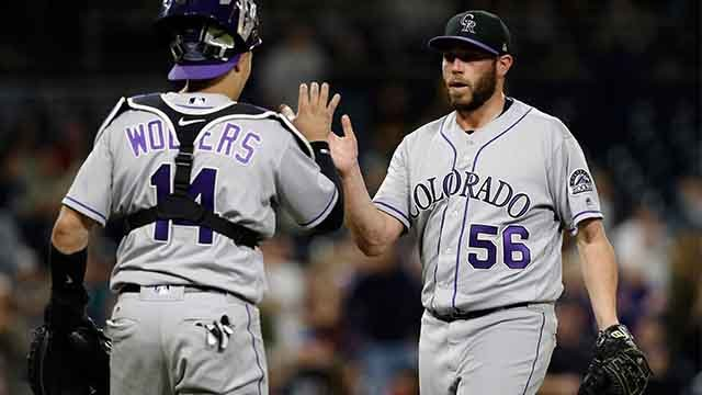 Colorado Rockies relief pitcher Greg Holland, right, gets congratulations from catcher Tony Wolters after their team defeated the San Diego Padres 4-1 in a baseball game in San Diego, Friday, Sept. 22, 2017. (AP Photo/Alex Gallardo)