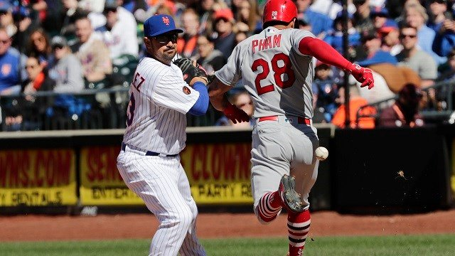 New York Mets first baseman Adrian Gonzalez (23) attempts to field the throw by third baseman Todd Frazier as St. Louis Cardinals' Tommy Pham (28) reaches first base during the sixth inning March 31, 2018, in New York. (AP Photo/Frank Franklin II)
