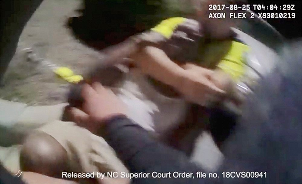 In this Aug. 25, 2017 image made from video and released by the Asheville, (N.C.) Police Department, Johnnie Jermaine Rush grimaces after officer Christopher Hickman overpowers Rush in a chokehold, in Asheville, N.C. (AP Images)