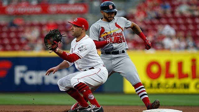 St. Louis Cardinals' Tommy Pham (28) is held to first base as Cincinnati Reds first baseman Joey Votto (19) takes the throw during the fourth inning of a baseball game, Friday, April 13, 2018, in Cincinnati. (AP Photo/Gary Landers)