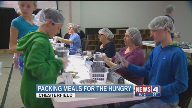 Volunteers help pack meals for families in need in Chesterfield. (Credit: KMOV)
