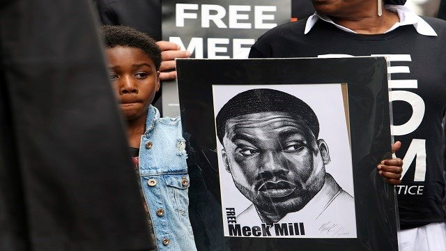 Rapper Meek Mill's son Papi holds a sign as protesters demonstrate in front of a courthouse during a hearing for Meek Mill, Monday April 16, 2018 in Philadelphia. (Credit: AP Photo/Jacqueline Larma)