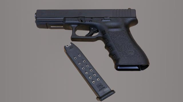 Glock Model 22 pistol with 15 shot magazine, graphic element on gray (Credit: AP Images)