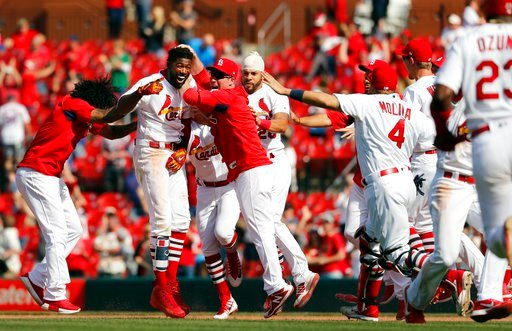 St. Louis Cardinals' Dexter Fowler, second from left, is congratulated by teammates after hitting a walkoff single during the 13th inning of a baseball game against the New York Mets, Thursday, April 26, 2018, in St. Louis. (AP Photo/Jeff Roberson)
