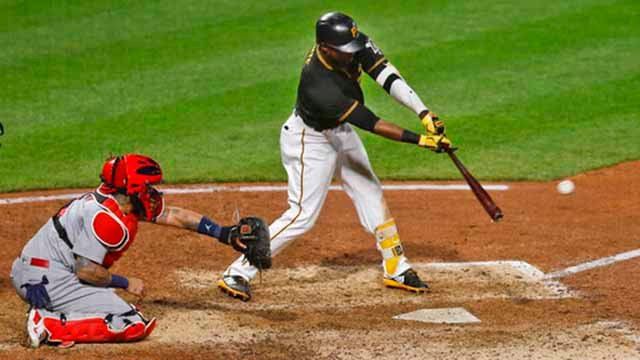 Pittsburgh Pirates' Starling Marte swings for a base hit in front of St. Louis Cardinals catcher Yadier Molina to drive in David Freese with the winning run in the 11th inning of a baseball game Friday, April 27, 2018, in Pittsburgh. The Pirates won 6-5.