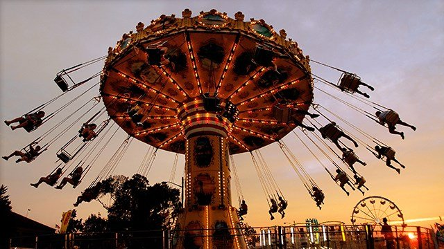 The sun sets as amusement rides and fun continue on opening day of the Illinois State Fair, Friday Aug. 12, 2011 at the Illinois State Fairgrounds in Springfield, Ill.  (Credit:AP Photo/Seth Perlman)
