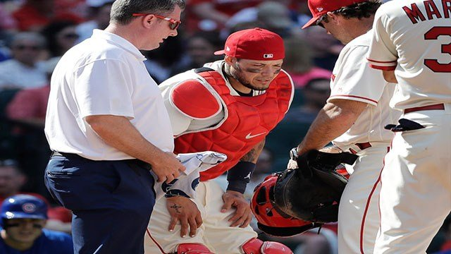 St. Louis Cardinals trainer Chris Conroy, left, and manager Mike Matheny, right, attend to catcher Yadier Molina after Molina was injured on a pitch during the ninth inning of a baseball game against the Chicago Cubs Saturday in St. Louis. (Credit: AP)