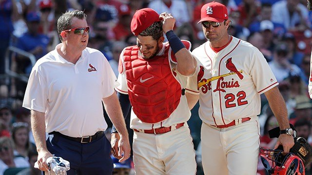St. Louis Cardinals trainer Chris Conroy, left, and manager Mike Matheny (22) take catcher Yadier Molina back to the dugout after Molina was injured on a pitch during the ninth inning of a baseball game against the Chicago Cubs, Saturday, May 5, 2018, in