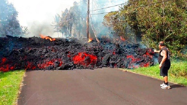 In this photo taken from video an unidentified man gets close to a lava flow advancing down a road in the Leilani Estates subdivision near Pahoa on the island of Hawaii Monday, May 7, 2018. Kilauea volcano has destroyed more than two dozen homes since it