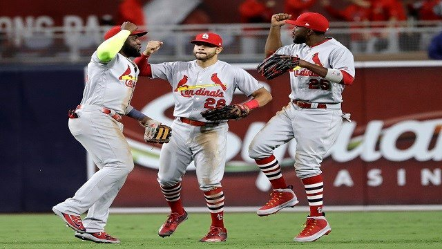 St. Louis Cardinals left fielder Marcell Ozuna, right, celebrates with center fielder Tommy Pham, center, and right fielder Tommy Pham after the Cardinals defeated the San Diego Padres 2-1 in a baseball game Thursday, May 10, 2018, in San Diego. (AP Photo