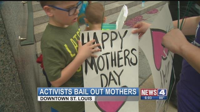 Attendes hold signs at the Bail Out Black Moms event in Downtown St. Louis. (Credit: KMOV)