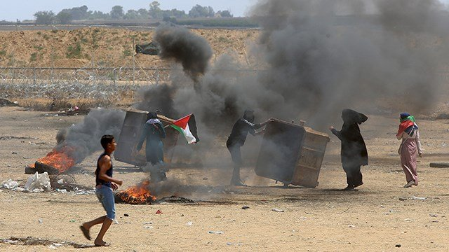 Palestinian protesters burn tires near the Israeli border fence east of Khan Younis in the Gaza Strip Monday