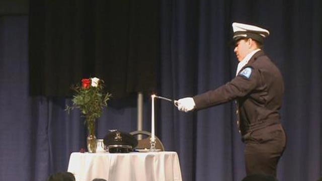 An officer lighting a candle in memory of fallen officers at the St. Louis Police Officer's Memorial Breakfast (Credit: KMOV)