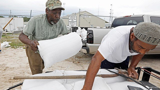 Tommy Whitlock, left, places a filled sand bag onto his trailer at a Harrison County Road Department sand bag location, as Joseph Buckner adjusts the load while preparing for Subtropical Storm Alberto to make its way through the Gulf of Mexico (Credit: AP