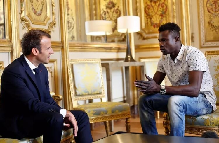 French President Emmanuel Macron (L) speaks with Mamoudou Gassama, 22, from Mali, at the presidential Elysee Palace in Paris, on May, 28, 2018. (CNN)