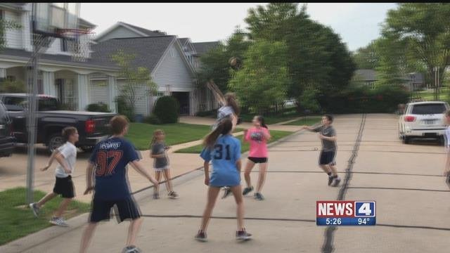 Kid playing basketball on a residential street in Sunset Hills. Credit: KMOV