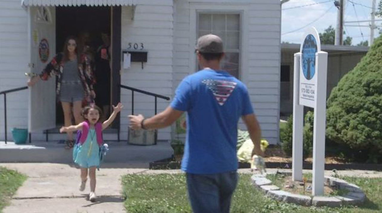 Solider Zach Clovis, right, surprises his daughter at her daycare after returning from a tour in Syria. (Credit: KMOV)