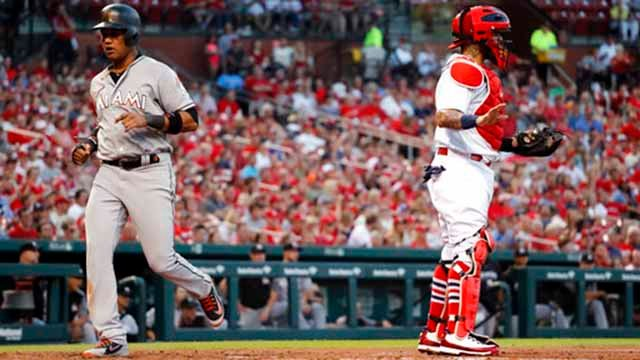 Miami Marlins' Starlin Castro, left, scores past St. Louis Cardinals catcher Yadier Molina during the third inning of a baseball game Tuesday, June 5, 2018, in St. Louis. (AP Photo/Jeff Roberson)