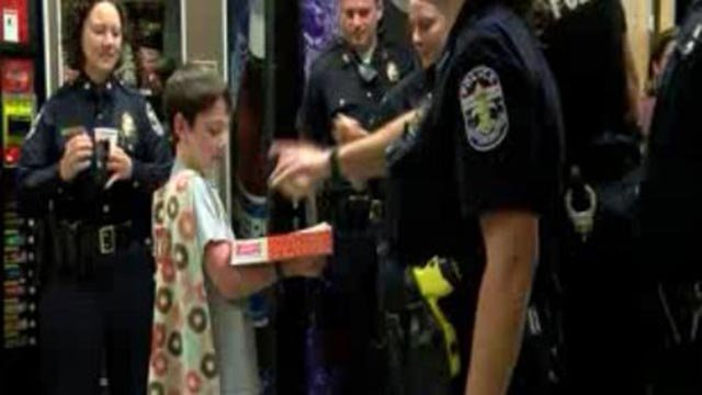 Tyler Carach, 10, is traveling the country passing out donuts to officers (Credit: KMOV)