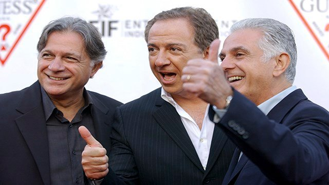 In this May 9, 2002 file photo, Guess Inc. founders and brothers, from left, Armand, Paul and Maurice Marciano arrive at the company's 20th anniversary party in Los Angeles. (Credit: AP Photo/Chris Pizzello, File)