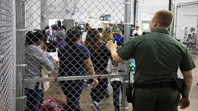 In this photo provided by U.S. Customs and Border Protection, a U.S. Border Patrol agent watches as people who've been taken into custody related to cases of illegal entry into the United States (Credit: U.S. Customs and Border Protection's Rio Grande Val