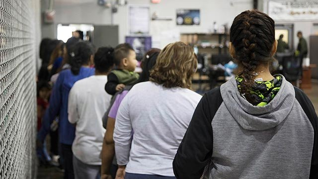 People who've been taken into custody related to cases of illegal entry into the United States, stand in line at a facility in McAllen, Texas, Sunday. (U.S. Customs and Border Protection's Rio Grande Valley Sector via AP)