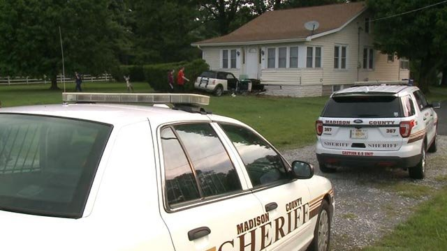 Deputies on the scene after a car hit a home in Alton Friday (Credit: KMOV)