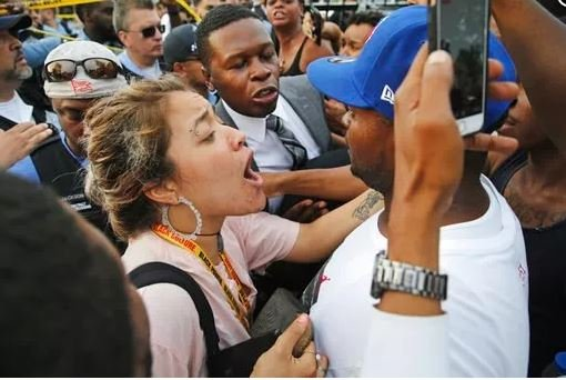 (Nuccio DiNuzzo/Chicago Tribune via AP). A woman tries to calm a man down as he yells at a police officer at the scene of a police involved shooting in Chicago, on Saturday, July 14, 2018.