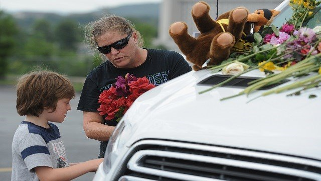 A family places flowers on vehicles of the victims of the Ride The Ducks accident on July 20, 2018 in Branson, Missouri. (Photo by Michael Thomas/Getty Images)
