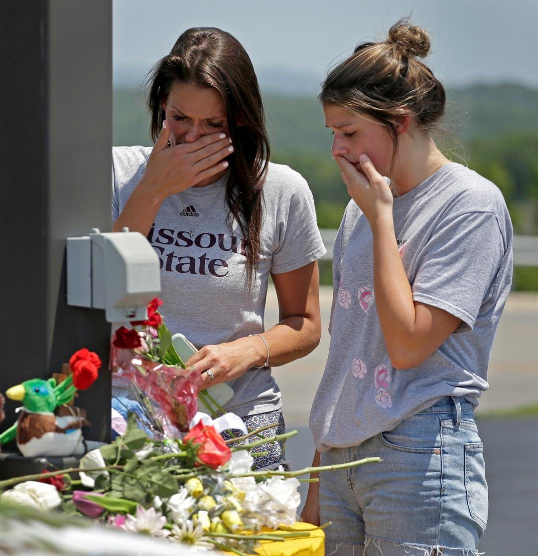 Rina Bernard, left, and Keri Johnson leave flowers on a car believed to belong to a victim of a last night's duck boat accident, Friday, July 20, 2018 in Branson, Mo.   (AP Photo/Charlie Riedel)
