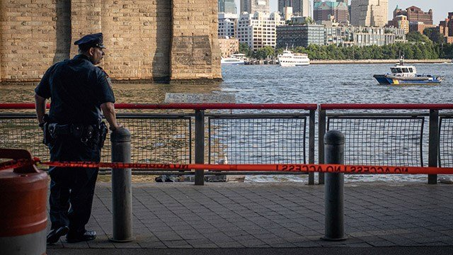A New York Police Department officer stands guard as authorities investigate the death of a baby boy who was found floating in the water near the Brooklyn Bridge in Manhattan, on Sunday, Aug. 5, 2018, in New York. (AP Photo/Robert Bumsted)