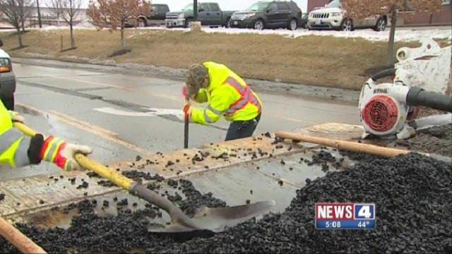 Street crews in Arnold, Mo. fill potholes during a respite from low temperatures in March.