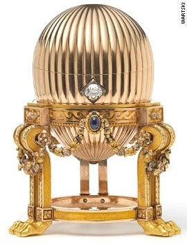 The 8.2-centimeter (3.2-inch) Faberge egg is on an elaborate gold stand supported by lion paw feet. Three sapphires suspend golden garlands around it, and a diamond acts as an opening mechanism. By Stephanie Baumer