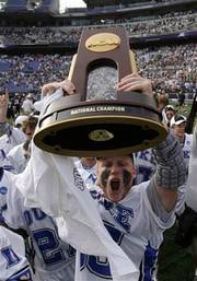 Duke's Parker McKee holds up the championship trophy after they defeated Notre Dame 6-5 in overtime to win the NCAA men's lacrosse tournament championship game Monday, May 31, 2010, in Baltimore.  (AP Photo/Rob Carr)