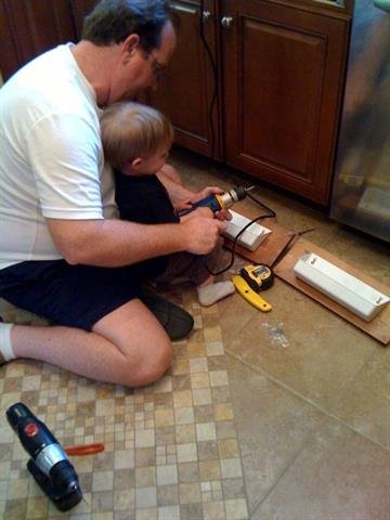Jude helping Uncle Lee (or UNK) install cabinets By Afton Spriggs