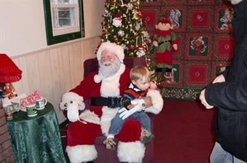 Jude tried to climb off Santa's lap to get back to Daddy. By Afton Spriggs