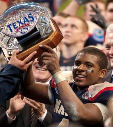 Navy quarterback Ricky Dobbs hoists the trophy following the Texas Bowl NCAA college football game against Missouri, Thursday, Dec. 31, 2009, in Houston. Navy defeated Missouri 35-13. (AP Photo/Dave Einsel) By Dave Einsel