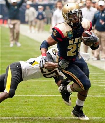 Navy's Marcus Curry (28) runs fo nine yards as Missouri's Kevin Rutland (20) defends during the first quarter of the Texas Bowl NCAA college football game Thursday, Dec. 31, 2009, in Houston. (AP Photo/Dave Einsel) By Dave Einsel