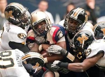 Navy quarterback Ricky Dobbs, center, is wrapped up by the Missouri defense during the first quarter of the Texas Bowl NCAA college football game Thursday, Dec. 31, 2009, in Houston. (AP Photo/Dave Einsel) By Dave Einsel