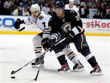 St. Louis Blues' Matt D'Agostini, right, and Chicago Blackhawks' Brent Seabrook chase a loose puck during the second period of an NHL hockey game Friday, Oct. 22, 2010, in St. Louis. (AP Photo/Jeff Roberson) By Jeff Roberson