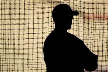 St. Louis Cardinals hitting coach Mark McGwire stands inside a batting cage as he works with Cardinals players during spring training baseball Wednesday, Feb. 17, 2010, in Jupiter, Fla. (AP Photo/Jeff Roberson) By Jeff Roberson