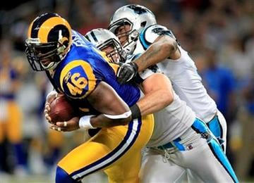 St. Louis Rams tight end Daniel Fells carries a pair of Carolina Panther defenders, Dan Connor, midddle, and Eric Norwood, during the second quarter of an NFL football game Sunday, Oct. 31, 2010, in St. Louis. (AP Photo/Jeff Roberson) By Jeff Roberson