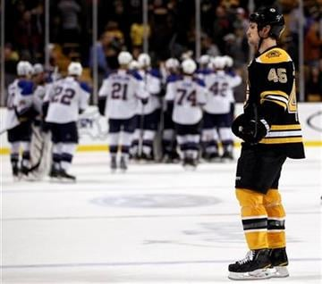 Boston Bruins defenseman Mark Stuart skates off the ice as St. Louis Blues celebrate their 2-1 shootout win in a NHL hockey game in Boston Saturday, Nov. 6, 2010. (AP Photo/Winslow Townson) By Winslow Townson