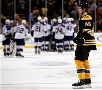 Boston Bruins defenseman Mark Stuart skates off the ice as St. Louis Blues celebrate their 2-1 shootout win in a NHL hockey game in Boston Saturday, Nov. 6, 2010. (AP Photo/Winslow Townson) By Winslow Townson