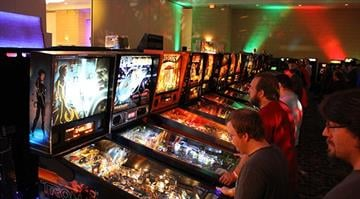 Gaming enthusiasts play pinball games at the Houston Arcade and Pinball Expo in November, 2012. By Stephanie Baumer